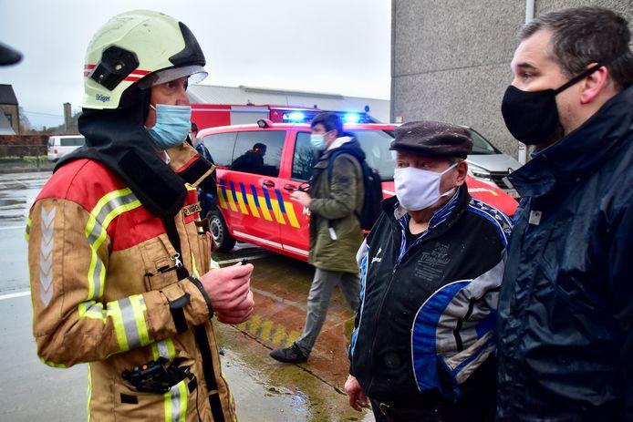 Bewoner Hilaire Vandemoortel (midden, met pet) en een van zijn zonen in gesprek met brandweerofficier Peter Vangierdegom.