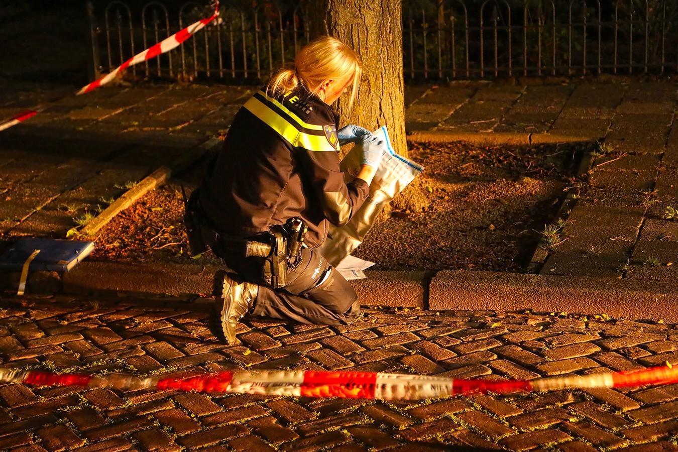 Een agente stelt sporen veilig na een autobrand aan de Ussenstraat in Oss.