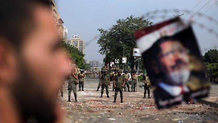 Een demonstrant staat bij een portret van de verdreven president Mohamed Morsi, dat aan een versperring van prikkeldraad is gehangen. Beeld ap