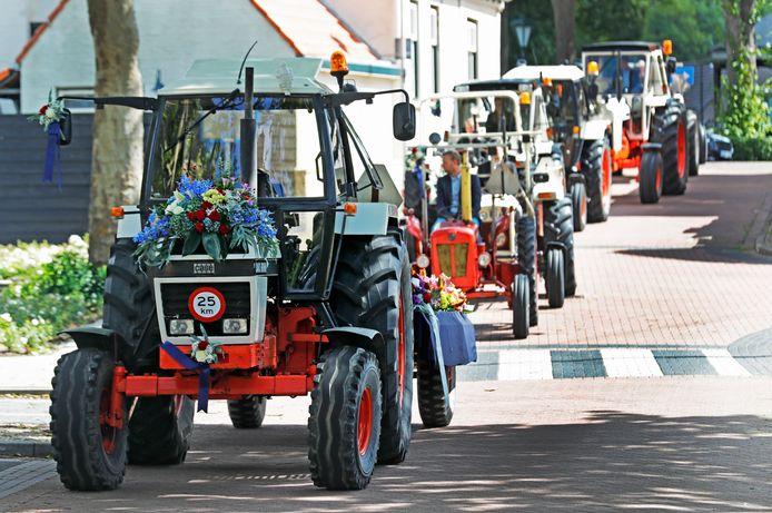 De tractoren rijden in een stoet naar de begraafplaats