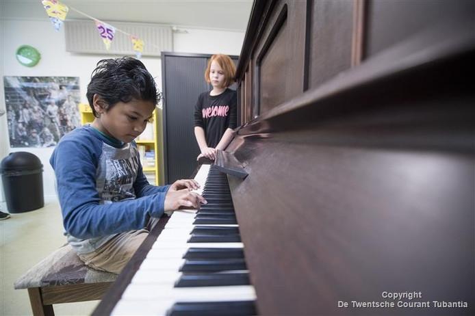 Jaëma bespeelt regelmatig de piano, die na de verbouwing op de gang staat. Klasgenoot Samira kijkt toe.
