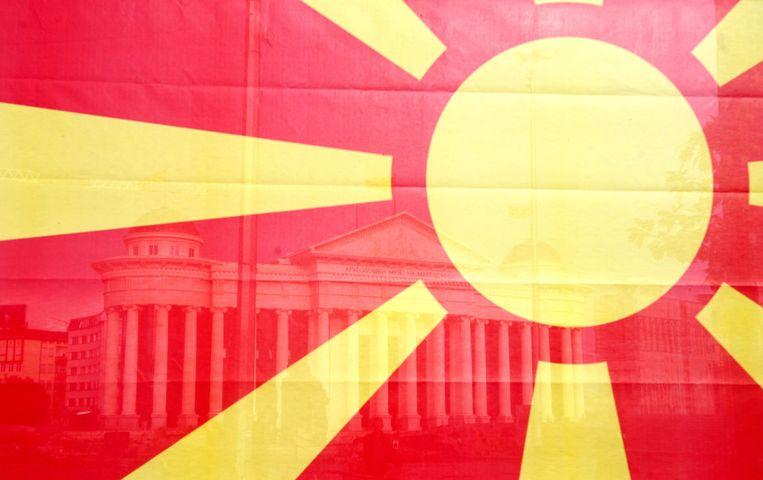 De Macedonische vlag, met op de achtergrond het Macedonische constitutionele hof in Skopje.  Beeld ANP