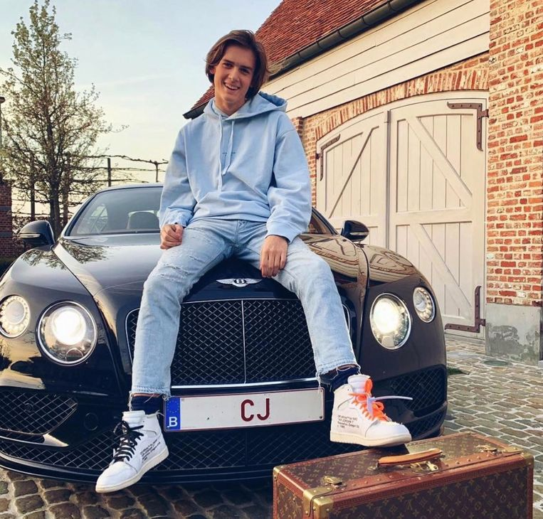 """Conrad Janssens zittend op zijn """"crazy"""" cadeau: een Bentley met instapprijs van 180.000 euro, de Off White-baskets van om en bij de 475 euro losjes op de Louis Vuitton-koffer van enkele duizenden euro's."""
