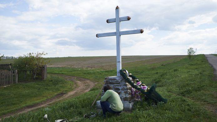 Een vrouw verzorgt het kruis bij de burnsite van vlucht MH17 van Malaysia Airlines. Rond de rampplek in Oost-Oekraine zijn veel van dit soort gedenktekenen te vinden.