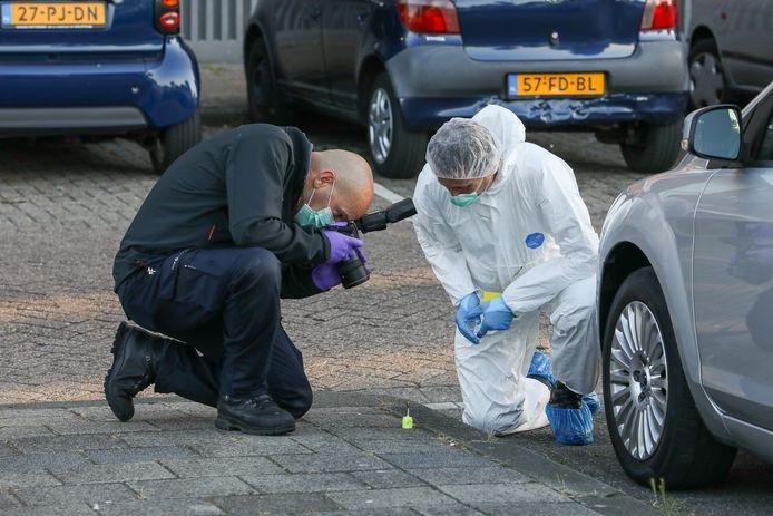 De forensische opsporing fotografeert aangetroffen kogelhulzen.
