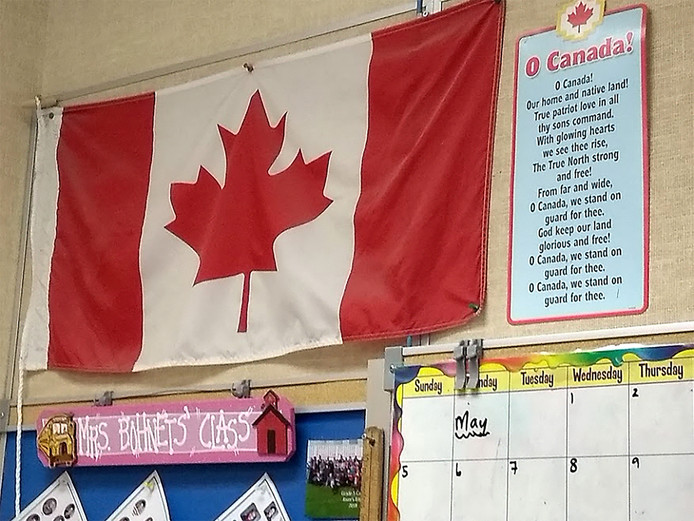 De Canadese vlag en de tekst van het volkslied aan de muur van een klaslokaal.