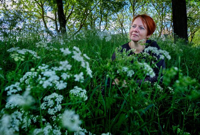 Martine van Wensveen tussen het fluitekruid aan de dijk tegenover haar huis.