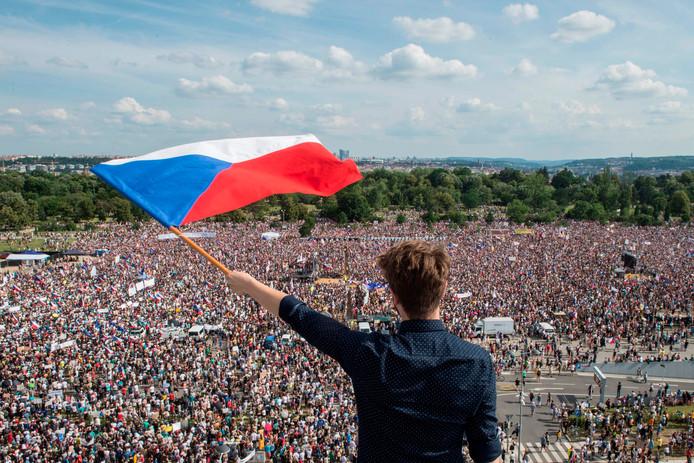 Een man zwaait met de Tsjechische vlag in wat 'de grootste demonstratie sinds de omwenteling' (1989) wordt genoemd.