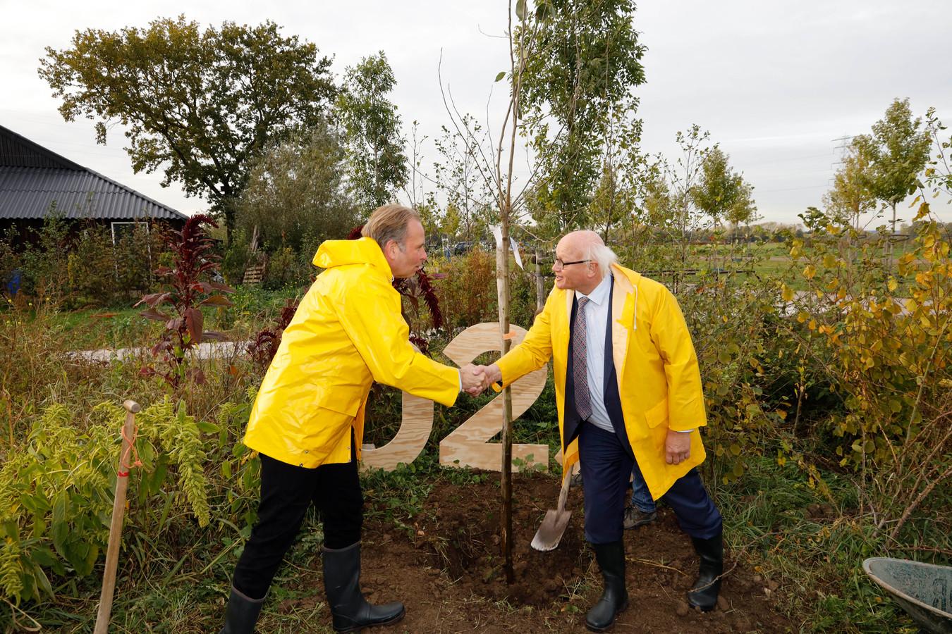 Wethouders Noël Vergunst (links, Nijmegen) en Hans de Vroome (Arnhem), schudden in Elst de hand in Elst na het planten van een appelboom.