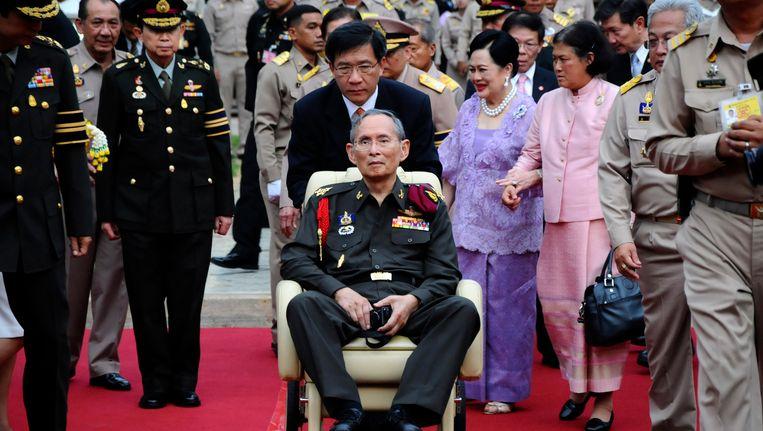 Koning Bhumibol wordt voortgeduwd in zijn rolstoel tijdens een bezoek aan een rijstveld in de provincie Ayutthaya. Beeld ap