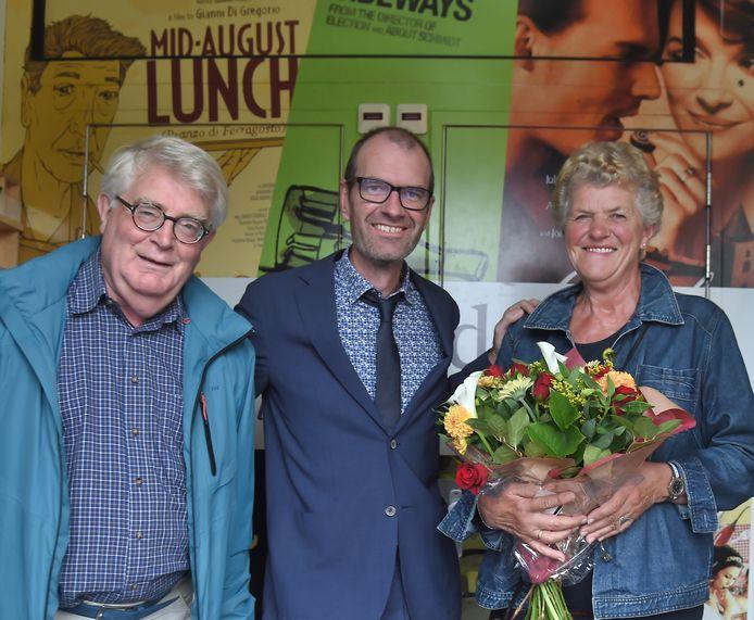 Directeur Simon Blaas (midden) zet het echtpaar Vuijk in de bloemetjes. Mevrouw Vuijk was de 100.000e bezoeker van Cinema Middelburg.