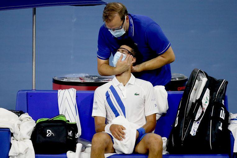 Djokovic wordt behandeld tijdens de wedstrijd. Beeld AFP
