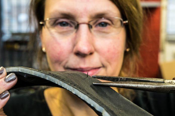 Fietsenmaker Zwaantje van Dijk haalt weer een ijzeren /stalen naald uit een fietsband afkomstig van veegmachines gemeente.