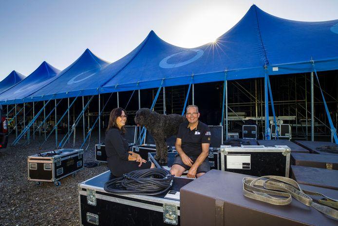 John van Pas met zijn vrouw Roos en hond Boris voor de tent waar hij een groot overdekt terras met live-muziek neerzet.