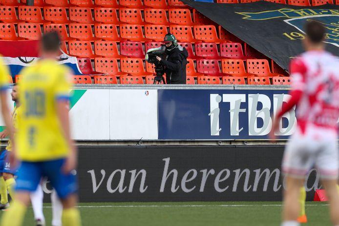 Voetbal in coronatijd. Geen kip meer op de tribunes, behalve een cameraman.