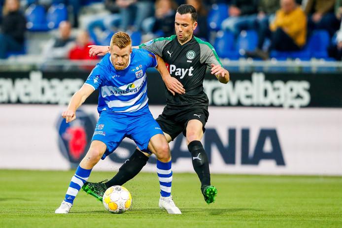 Thomas Bruns voor FC Groningen in duel met Mike van Duinen van PEC Zwolle.