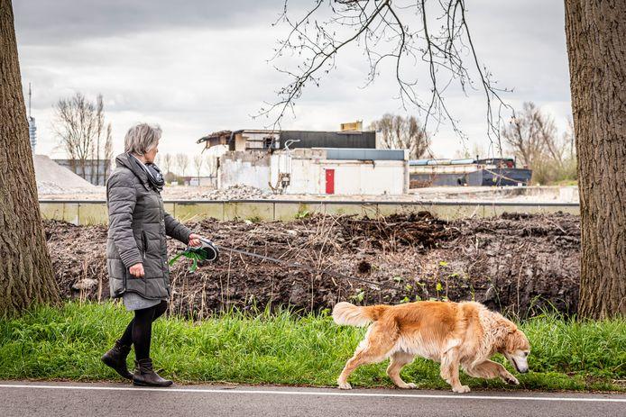 Een buurtbewoonster loopt langs het bouwterrein aan de Staalweg in Alphen, waar een een recyclingfabriek voor plastic zou komen.