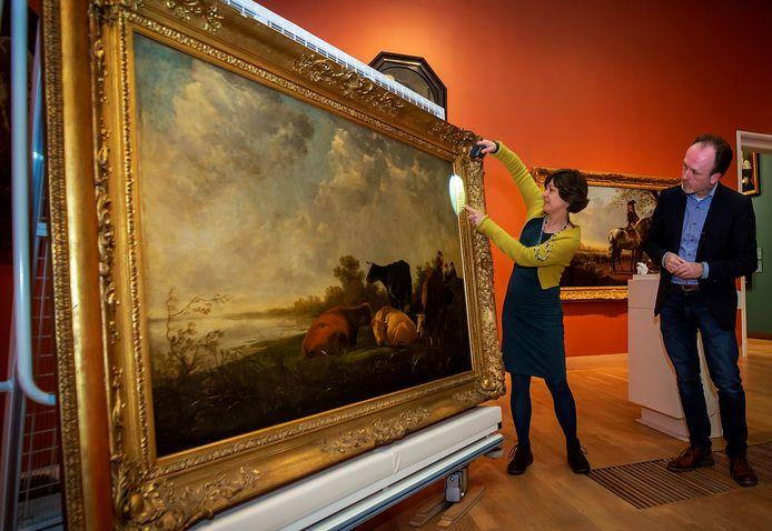 Lidwien Speleers, hier samen met de conservator, restaureert het 350 jaar oude schilderij Rivierenland in het Dordtse museum. Met het schilderij was de lokale schilder Aelbert Cuyp enorm populair in Engeland.