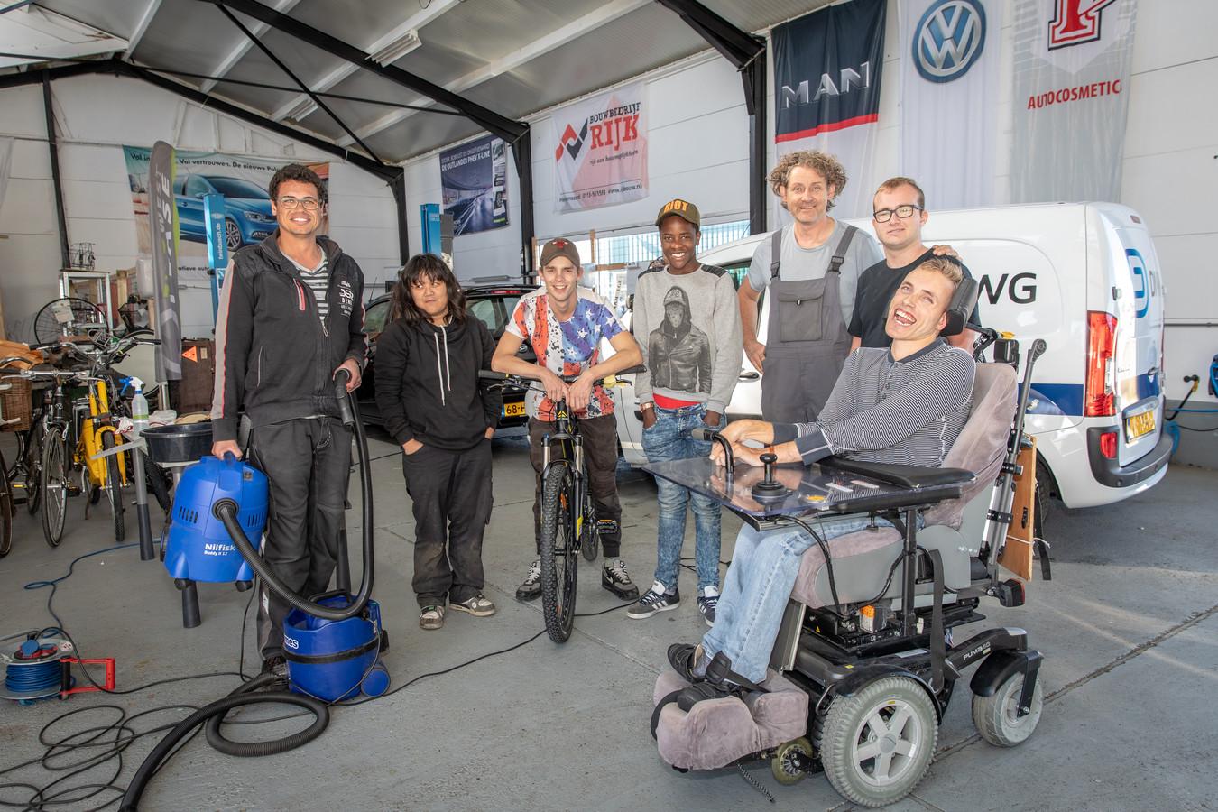 Renaldo, Rizan, Jiany, Shafik, eigenaar Leonard Koppelaar, Florian en Jelle in de loods van autopoetsbedrijf SAV in Goes.