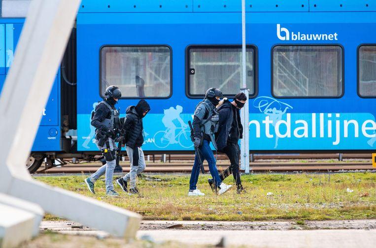 Leden van het arrestatieteam voeren twee verdachten af uit een trein op station Zwolle. Beeld null
