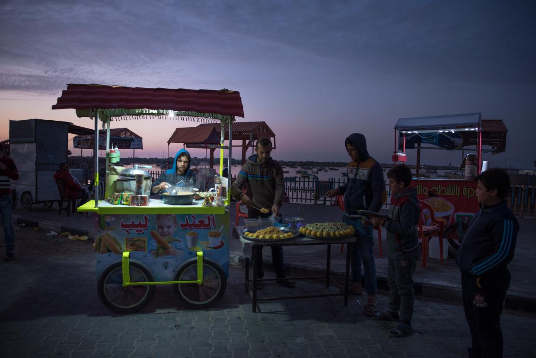 Jongeren in Gaza bereiden snacks onder ledverlichting op batterijen. Beeld Chloe Sharrock / Le Pictorium