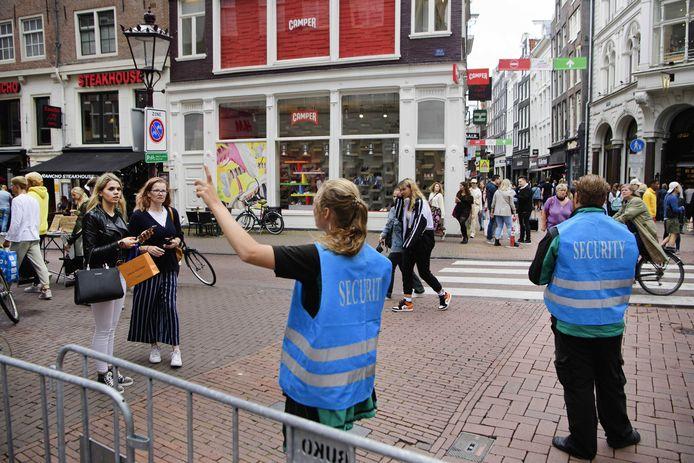 Handhavers begeleiden toeristen in het centrum van de stad.