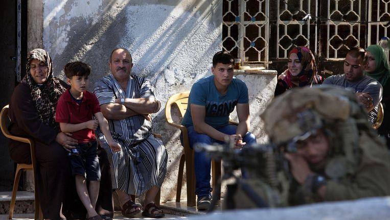 Een Palestijnse familie kijkt naar Israëlische soldaten die patrouilleren door Hebron Beeld ap