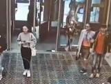 Vrouw kijkt op telefoon en loopt door glazen wand