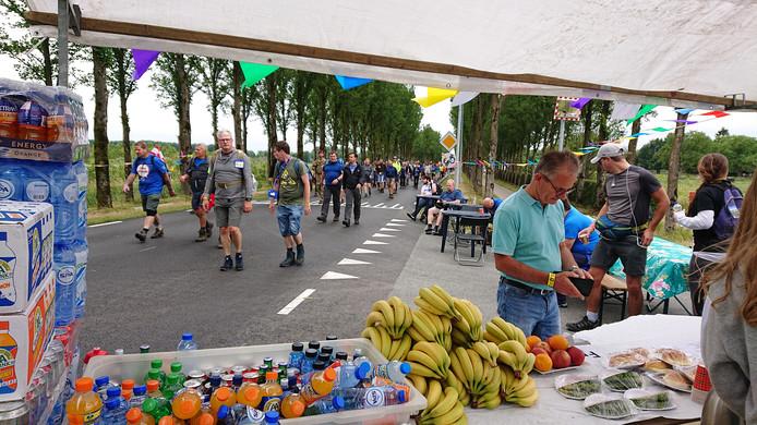 Vierdaagsewandelaars lopen over de Rijksweg Noord in Elst in de richting van Elden. Onderweg zijn er versnaperingen voor wie wil.