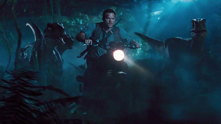 Chris Pratt rijdt op een motor naast velociraptors in Jurassic World. Beeld null