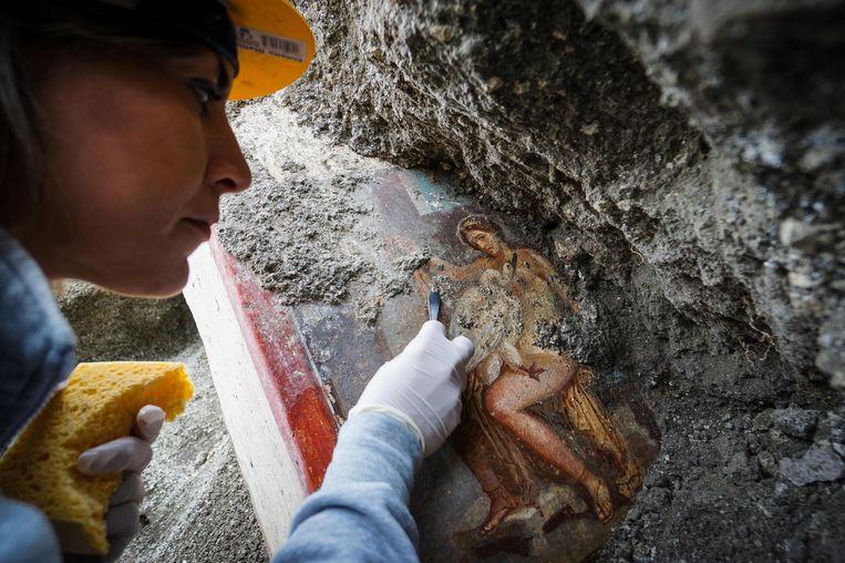 Een archeoloog werkt aan het nieuw ontdekte fresco Leda en de zwaan, in Pompeii.  Beeld EPA