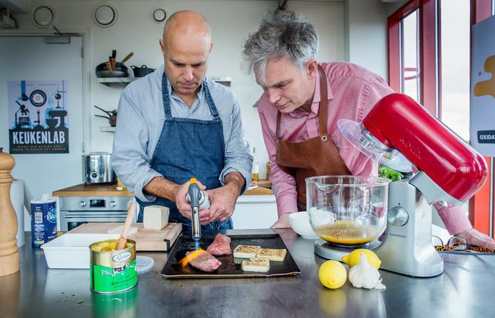 Chef Eke Mariën (links) en wetenschapper Jan Groenewold demonstreren de maillardreactie met een gasbrander, maken chocolademousse met stikstof en maken een meloencocktail met een vacüumzuiger.