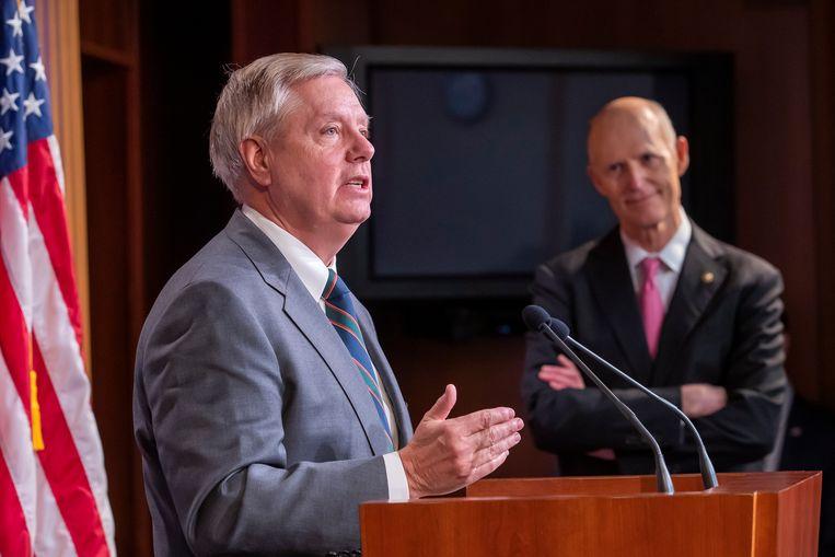 Republikeinse senatoren Lindsey Graham (links) en Rick Scott op een persconferentie over het steunpakket in het Capitool in Washington. Beeld EPA