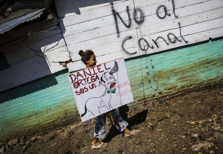 Een meisje draagt een getekend protestbord tegen de aanleg van het kanaal: president 'Daniel Ortega je bent een .... verkoopt het vaderland.' Haar dorp bij het Nicaraguameer moet weg. Beeld Inti Ocon / AFP