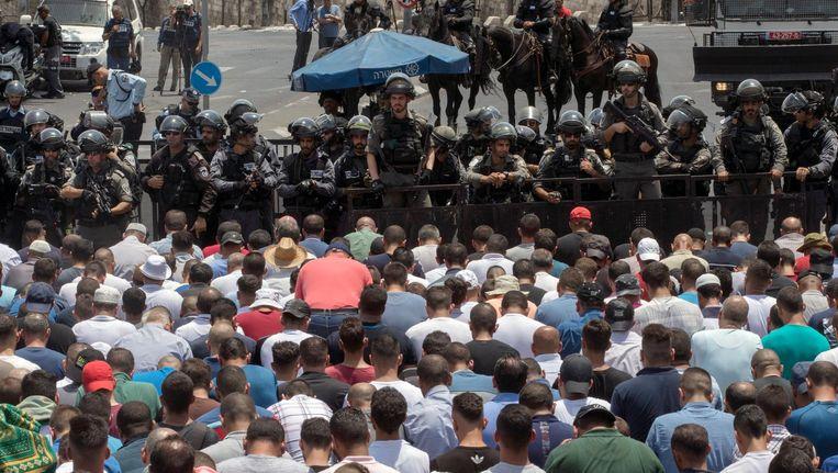 Palestijnen bidden voor een rij Israëlische agenten. Uit protest tegen aangescherpte veiligheidsmaatregelen vond het massagebed buiten de Al Aqsa-moskee plaats. Beeld epa