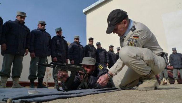 Een Duitse politieman traint Afghaanse politiemensen in opleiding. © anp Beeld