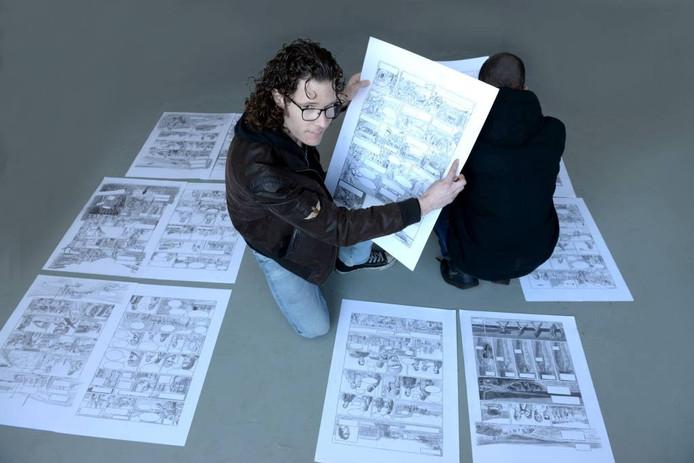 Jules Calis in zijn atelier, omringd door diverse schetsen van zijn stripboek 'Vluchteling'. De hoofdpersoon van het verhaal, Youssef, zit naast hem. Met zijn rug naar de fotograaf toe, omdat hij niet wil dat zijn identiteit bekend wordt.