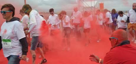 Rennen door een gordijn van kleurpoeder tijdens de Colorrun in Tholen