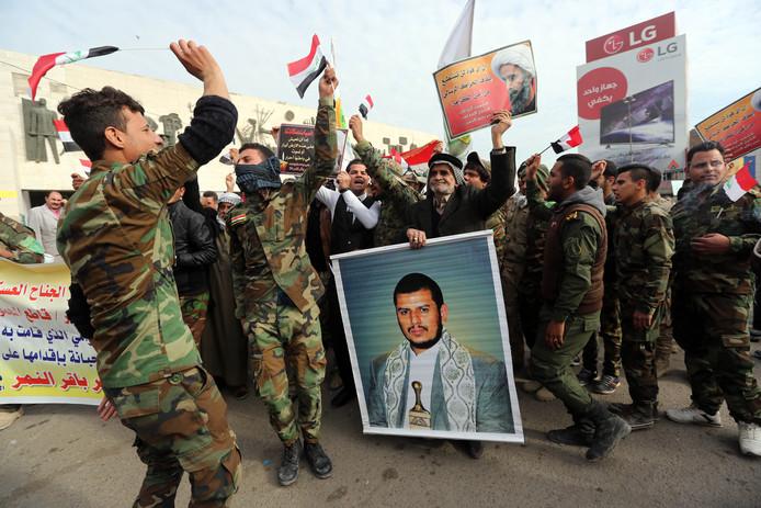 Houthi-strijders dragen een portret Abdul-Malik al-Houthi.