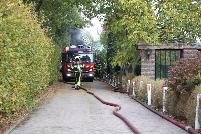 De brandweer probeert de slecht bereikbare stal te blussen.