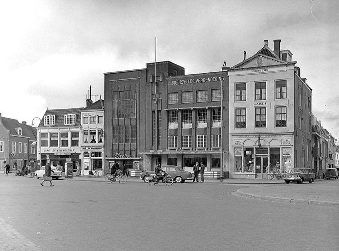 Sociëteit de Vergenoeging op de Markt van Middelburg, anno 1962. Vanaf links café De Vriendschap, café De Koophandel en bioscoop Electro, dan De Vergenoeging, rechts het pand De Roode toren. foto-archief PZC, Beeldbank Zeeland, recordnr FO132536