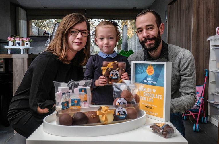 Papa Pieter, mama Jessy en dochtertje Marlou verkopen samen chocolade om de dienst neonatologie van het AZ Sint-Jan te steunen.
