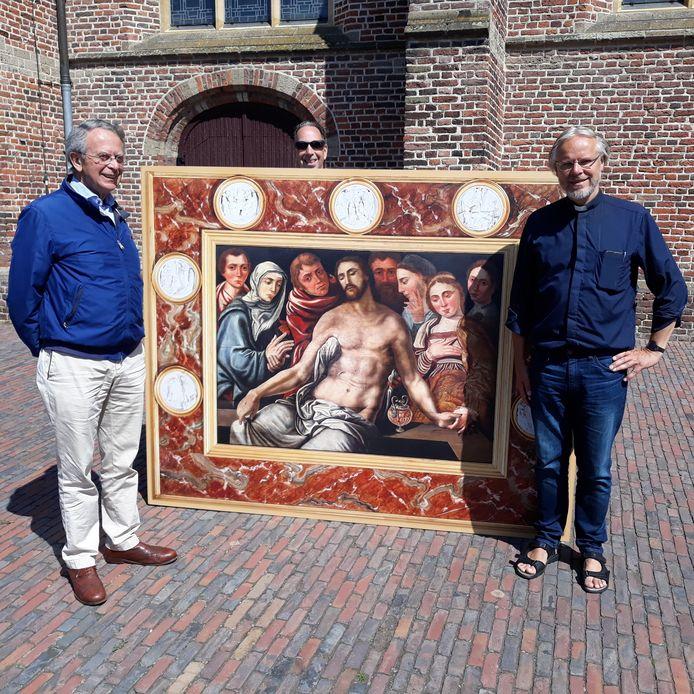 Jan van Homelen (links) draagt het tableau over aan pastoor Geertjan van Rossem (rechts) bij de ingang van de Sint-Petrusbasiliek in Boxtel. Daar krijgt het stuk een vaste plek. In het midden bestuurslid Arnold van den Broek van de Heilig-Hartparochie.
