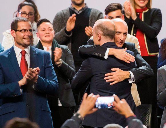 Oud-premier en partijleider Joseph Muscat wordt door Chris Fearne omhelsd. Links kijkt de nu verkozen premier Robert Abela toe.