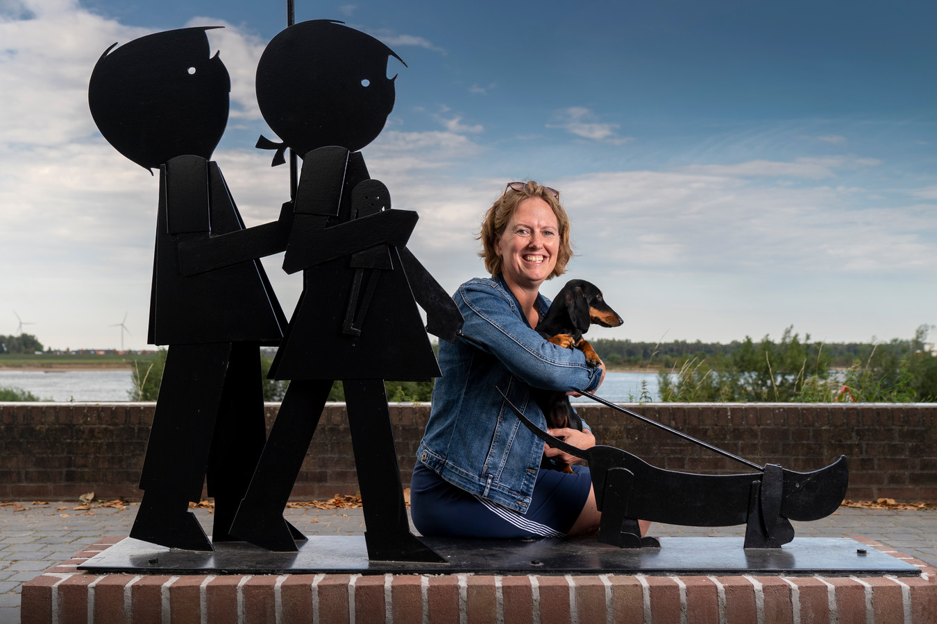 Esther Zumpolle met teckel Joeks bij het beeld van Jip en Janneke met Takkie op de Waalkade in Zaltbommel.