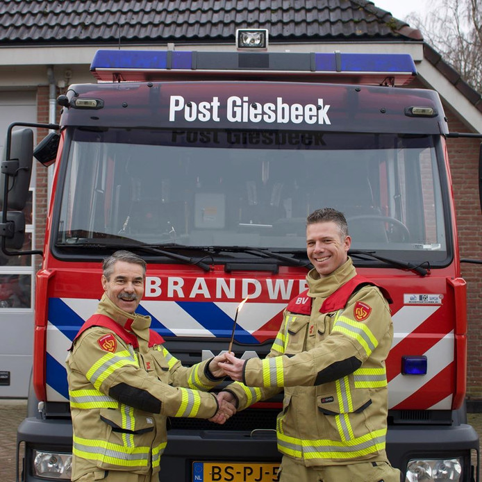 Brandweercommandant Hans Verhoef (l) draagt letterlijk het stokje over aan Maarten Soethof.