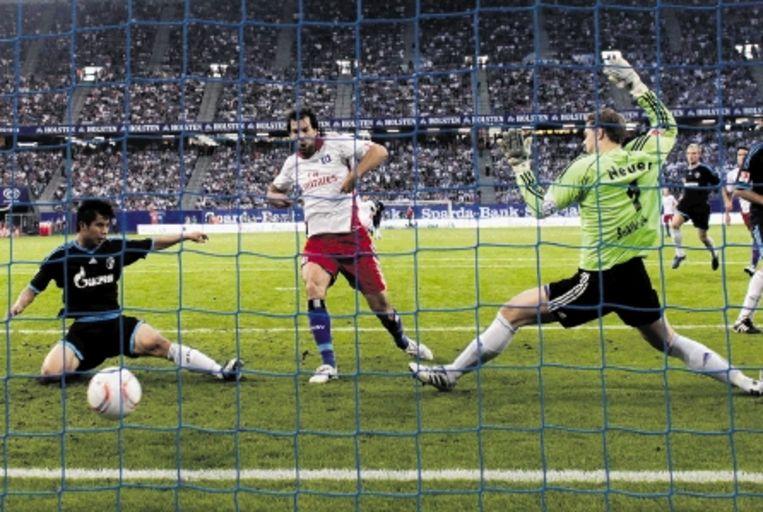 Van Nistelrooij maakt de winnende treffer (2-1) voor HSV tegen Schalke?04 in het openingsweekeinde van de Duitse competitie. De Chinees Junmin Hao en doelman Neuer kunnen het niet meer verhinderen. Eerder had Van Nistelrooij ook het eerste doelpunt van HSV al op zijn naam geschreven. (FOTO AP) Beeld
