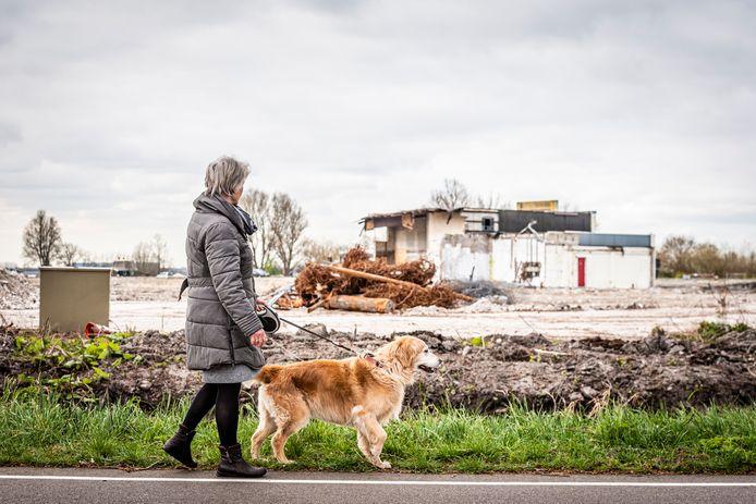 Buurtbewoonster loopt langs het bouwterrein aan de Staalweg 4
