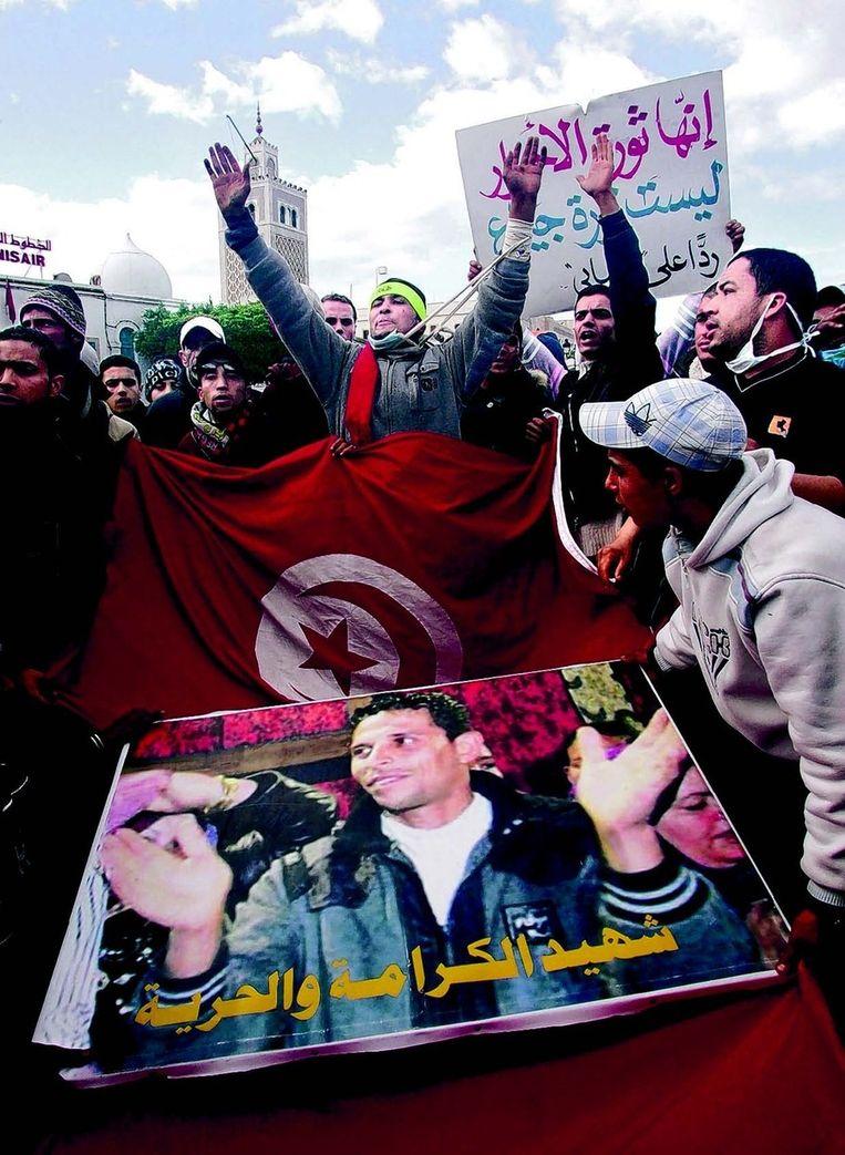 Demonstranten dragen in Tunis het portret van Mohammed Bouazizi die zichzelf in brand stak in 2010. Beeld EPA