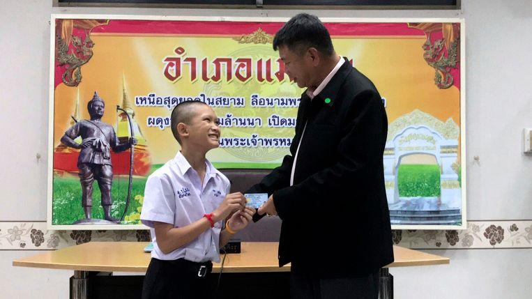 Mongkol Boonpiam, een van de geredde voetballertjes, krijgt een Thaise identiteitskaart van de lokale sheriff Somsak Kunkam.